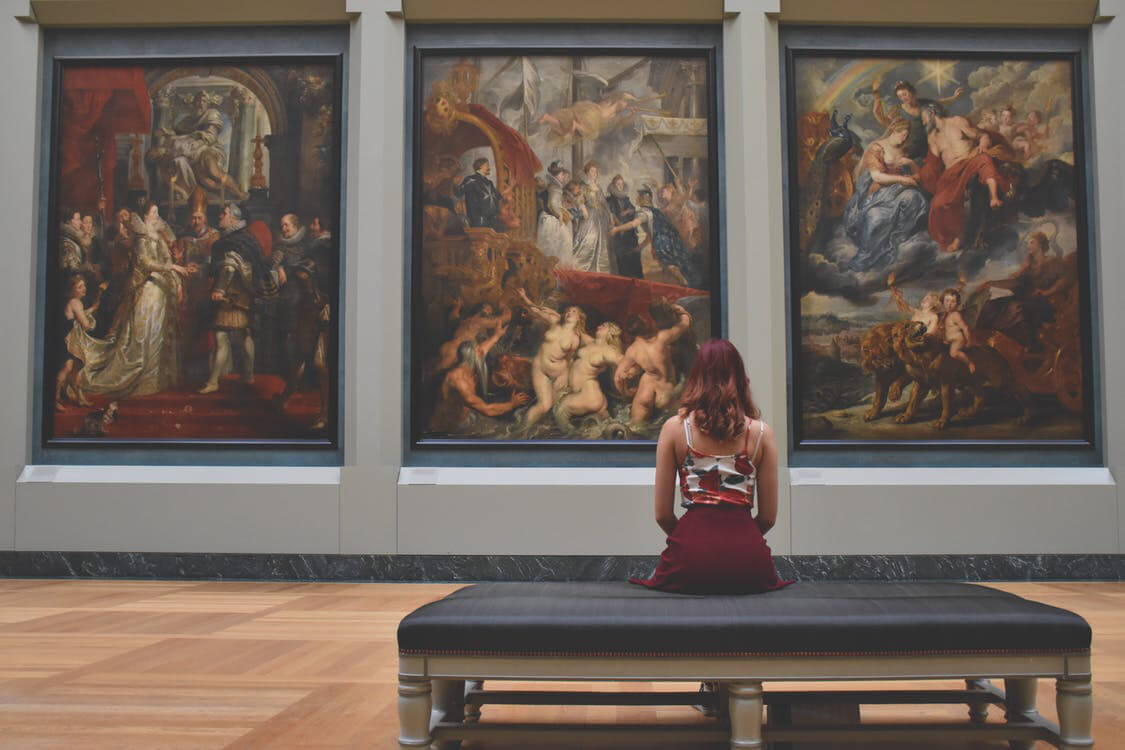 person viewing paintings